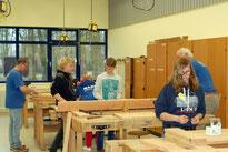 Bild: Emsig bauen Jugendliche aus der achten Klasse gemeinsam mit NABU-Ehrenamtlichen an den Hochbeeten. Bis Ende März müssen sie fertig sein.