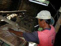 Holzteile werden aus Brettern gesägt.