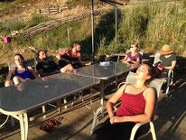 un groupe de stagiaire en repos autour d'une table profitant du soleil avec Juliette ADDESSO lors d'un stage bien être au gite de la Gorre Ardéche