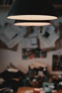 Spezialistenwissen für Mantel Liebhaber: Aufnahme von Arbeitsleuchten über dem Zuschneidetisch im Atelier von Manuela Leis