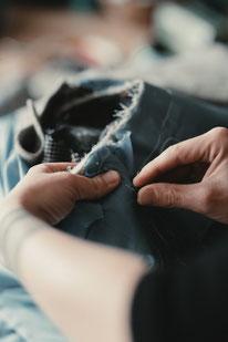 Mantelpflege und Reparatur: Aufnahme von Manuela Leis beim Austausch eines kaputten Ärmelfutters