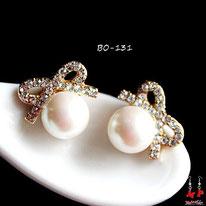 Boucles d'oreilles noeuds papillons dorés et strass avec une perle nacrée