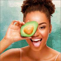 Mädchen hält sich eine Avocado vor das Gesicht