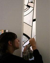 Lors de la pose  Marion Rusconi nettoie l'une de ses créations, un vitrail style art déco.