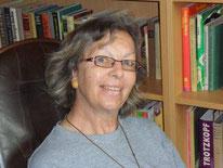 Autorin Elfride Stehle sitz vor ihrem Bücherregal.