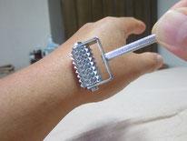 手首の腱にローラー針をかけています。