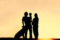 Une famille le pére la mére un jeune enfant et leur chien adulte regardent un coucher de soleil par coach canin 16