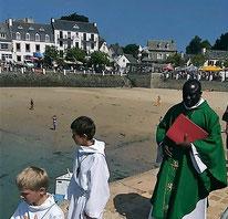 Le père Yves Tano ferme la procession, accompagné des servants d'autel.