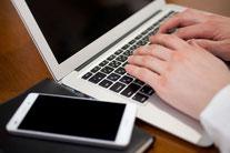 ノートパソコンとスマホを使う男性
