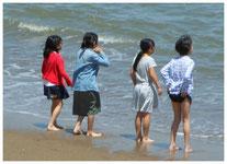 小学生が福祉ホテル「かしの木」に体験学習を行ったときの近くの海岸で遊んでいる様子。