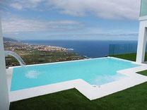 Blick vom Apartment vorbei an Palmen und dem Pool bis zum Horizont über dem Meer.