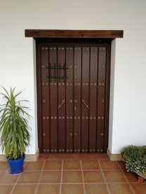 Puerta de aluminio blindada con postigo.