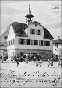 Man sieht eine hochkantige Postkarte mit in schwarz/weiß. In der Bildmitte ist das Rathaus in Flein, davor sind Menschen. Unten sind zwei Zeilen in Handschrift geschrieben.