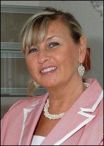 Renate Bach mit einem rot/weißen Jacket schaut und lächelt zur Kamera. Sie trägt Ohrringe und eine Perlenkette.