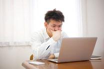 ノートパソコンを使う20代男性