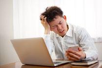 日本 ノートパソコンとスマホを使う20代男性