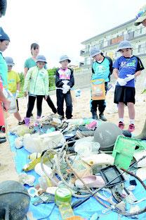 漂着ゴミをテーマにした劇を発表するため実際に漂着ゴミを拾い仕分けを行った海星小3年生ら=12日午後、大浜海岸