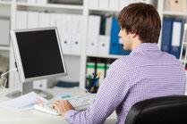 Homme en train d'écrire au clavier d'ordinateur