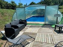 La piscine privative de couleur bleue avec un dallage blanc tout autour et sous serre du gite de la gorre en location en ardeche village de roiffieux