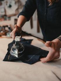 photo by Sebastian Hilgetag, Dressurbügeln eines Rückenteils, Aufnahme von Bügelarbeit mit Focus auf das Bügeleisen mit keiner Galleonsfigur am Griff