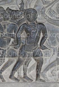 Tambour à deux membranes porté autour du cou et percuté avec deux baguettes. Angkor Vat, Défilé Historique. XIIe s.