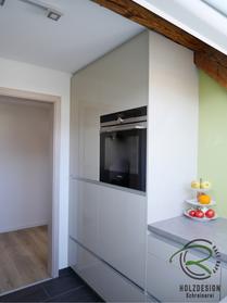 Hochschrankzeile mit Kühlschrank, Backofen und hoch eingebauter Spülmaschine unter Dachschräge