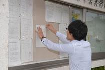 住民投票を告示する書類を市役所前の掲示板に貼る職員=31日午前