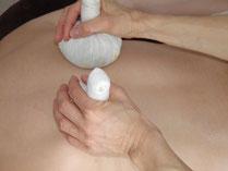 Massage du dos avec des pochons aux herbes aromatiques