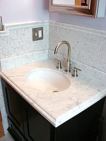 A marble bathroom vanity and matching backsplash on espresso brown cabinets.