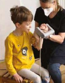 Kind mit neurologischer Erkrankung mit Vibrationshantel Galileo in der Hand und Ergotherapeutin