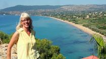 Blonde Frau kauert am Strand, im Hintergrund Meer und Wolkenhimmel.