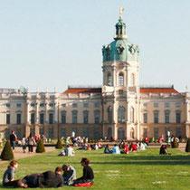 Menschen sitzen auf dem Rasen im Mai vor dem Schloss Charlottenburg. Foto: Helga Karl