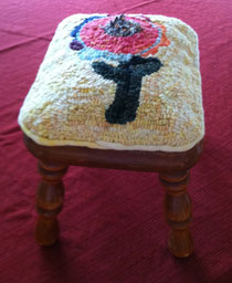 Hooked rug with hand-dyed wool attached to footstool.