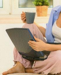 Studieren wo es am schönsten ist - mit Kaffeetasse und Laptop auf dem Teppich