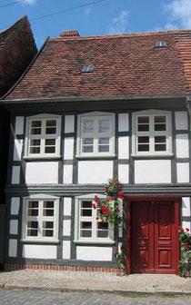 Fachwerkhaus mit roter Tür, grauen Balken und weißem Gefache