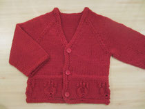 A red child's cardigan with paw prints around the hem