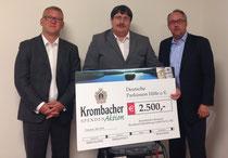 Uwe Köhler, Krombacher Verkaufsleiter (l.), überreichte an Ingo Jeschke und Stephan Goericke (r.) den Scheck