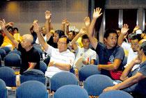 八重山漁協の総会で、日台漁業取り決めの白紙撤回に賛成して挙手する組合員=29日午後、市民会館中ホール