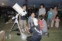 会場に設置された天体望遠鏡で月を観察する観客たち=2日夜、南ぬ浜町緑地公園