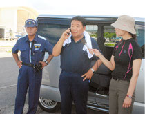 水産庁の職員と電話で押し問答する水島氏(中央)=20日午前、登野城漁港