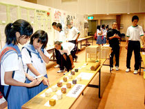 八重山地区中学校総合文化祭が始まった。展示作品を眺める中学生たち=10日午後、市民会館中ホール