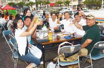 交流会は中国語と日本語、ウチナーグチが飛び交った。ビールで互いの健闘をたたえ合うヨットマンら=石垣港
