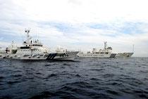 高洲丸に異常接近する「海監15」(右)と、割って入る海保の巡視船=13日午後、南小島の東南2㌔、高洲丸船上より撮影