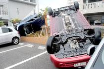 突風で横転した乗用車=13日午前9時ごろ、浜崎町の東横イン石垣島の駐車場