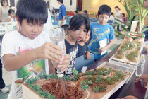 「赤土deふぇすてぃばるin石垣」で、赤土流出防止の仕組みを学ぶ参加者=23日午後、大浜公民館