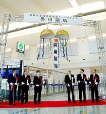 那覇空港の新国際線ターミナルビルの運用開始を祝い、くす玉を割る関係者=17日