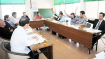 休憩中に挙手でPC3配備決議の賛否を確認する議会運営委員会。右側が与党=26日午前、市役所