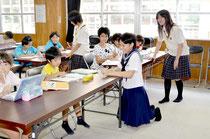 制服姿の高校生指導員が、児童の勉強にアドバイスした=八島小学校