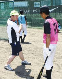 中学生にバッティング指導する久慈照嘉さん(左)=市中央運動公園野球場