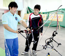 山田事務局長(左)から弓について教えてもらう高那君(右)=12日午前、櫻花ビル内